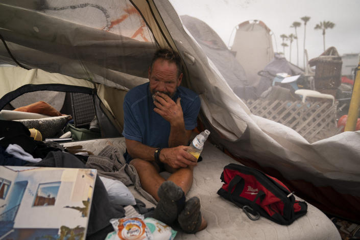 FILE - In this June 29, 2021, file photo, Scott See passes time in his tent at a homeless encampment set up along the boardwalk in the Venice neighborhood of Los Angeles. The recall election that once threatened Gov. Gavin Newsom's political career has instead given it new life, The rare midterm vote of confidence could fuel an ambitious legislative agenda featuring new coronavirus vaccine mandates, housing for the homeless and health insurance for people living in the country illegally. (AP Photo/Jae C. Hong, File)