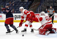 Detroit Red Wings goalie Calvin Pickard, right, makes a stop behind Columbus Blue Jackets forward Nathan Gerbe, left, and Red Wings defenseman Gustav Lindstrom during the second period of an NHL hockey game in Columbus, Ohio, Saturday, May 8, 2021. (AP Photo/Paul Vernon)