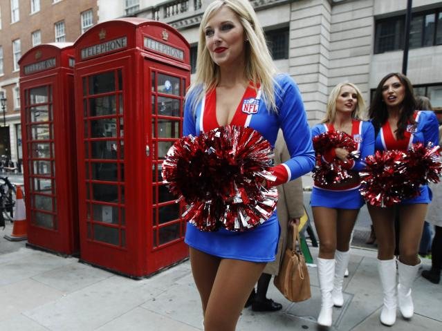 Cheerleaders from the NFL pass traditional phone boxes during a 'block party' on London's Regent Street ahead of NFL matches between Pittsburgh Steelers versus the Minnesota Vikings and San Francisco 49ers versus the Jacksonville Jaguars in London September 28, 2013. REUTERS/Luke MacGregor (BRITAIN - Tags: SPORT SOCIETY)