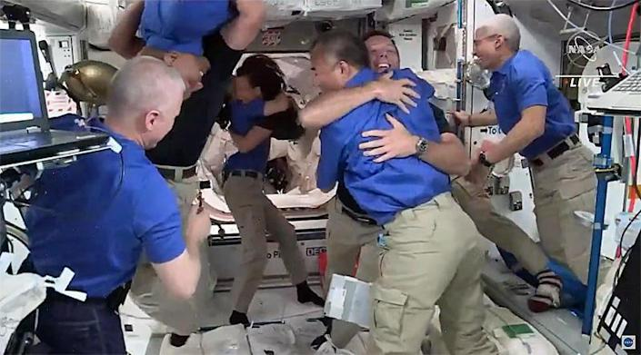 The space station's seven-member crew welcomed the Crew-2 astronauts aboard the station with smiles, hugs and handshakes. / Credit: NASA TV