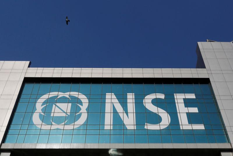 A bird flies past the logo of National Stock Exchange (NSE) installed on the facade of its building in Mumbai