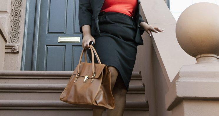A woman walks down stairs from her front door carrying a handbag.