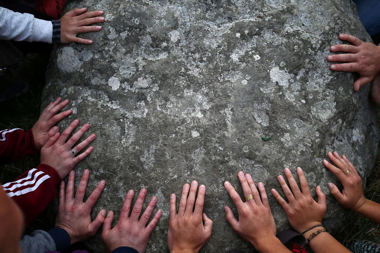 <p>People touch the stones of the Stonehenge monument at dawn on the summer solstice near Amesbury, Britain, June 21, 2017. (Photo: Neil Hall/Reuters) </p>