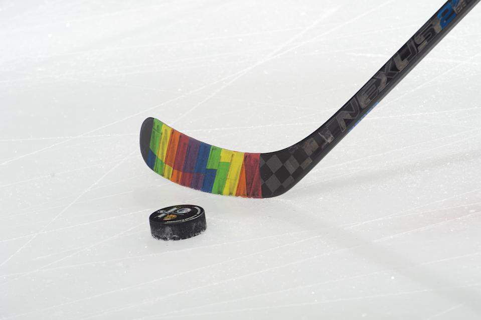 A hockey stick is taped in rainbow colors near a hockey puck.