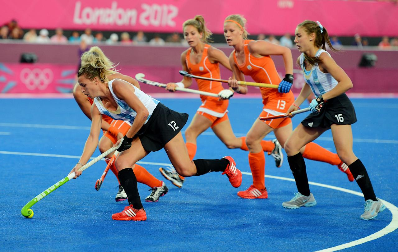 LONDON, ENGLAND - AUGUST 10:  Delfina Merino #12 of Argentina controls the ball against the Netherlands during the first half of the Women's Hockey gold medal match on Day 14 of the London 2012 Olympic Games at Hockey Centre on August 10, 2012 in London, England.  (Photo by Mike Hewitt/Getty Images)