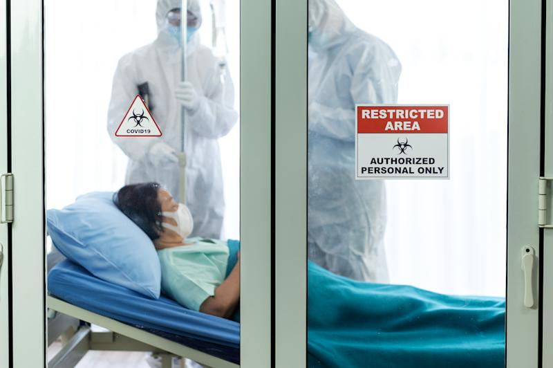 Restricted area and covid-19 signs in front of the clean room with doctors and patient background