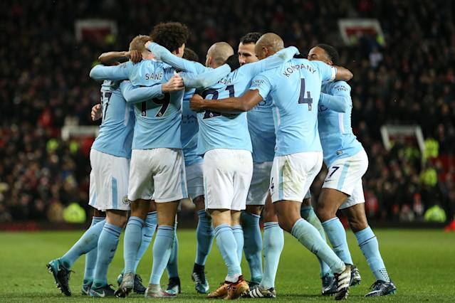 Manchester City celebrates one of its two goals against Manchester United at Old Trafford on Sunday. City won 2-1. (Getty)