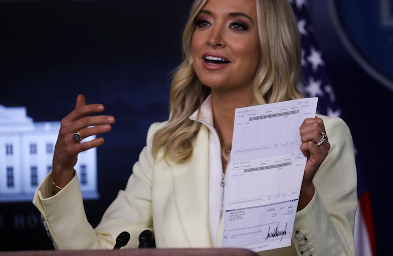 "White House press secretary Kayleigh McEnany holds up a donation check signed by Donald Trump for $100,000 made out to the ""Office of the Assistant Secretary for Health"" — complete with bank account details. (Photo: Leah Millis/Reuters)"