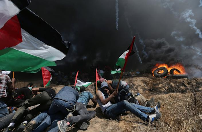 Palestinian demonstrators take cover from Israeli fire and tear gas during a protest against U.S. embassy move to Jerusalem. (Photo: Ibraheem Abu Mustafa / Reuters)