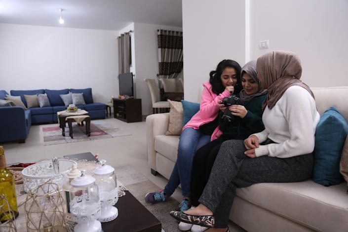 "Nada Rudwan, center, 27, who used to work in digital marketing, looks at videos of herself cooking that were filmed by her sister, Lama Rudwan, right, 22, at their home in Gaza City on Dec. 16, 2018. ""It was difficult to find a job, so I thought of doing something I like and that will make me money at the same time,"" said Rudwan, who posts cooking tutorials to social media platforms under the name Nada Kitchen. (Photo: Samar Abo Elouf/Reuters)"