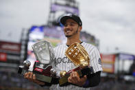 Colorado Rockies third baseman Nolan Arenado smiles as he holds up the Platinum and Golden Glove for his fielding play last season during a ceremony before a baseball game against the Los Angeles Dodgers Saturday, April 6, 2019, in Denver. (AP Photo/David Zalubowski)