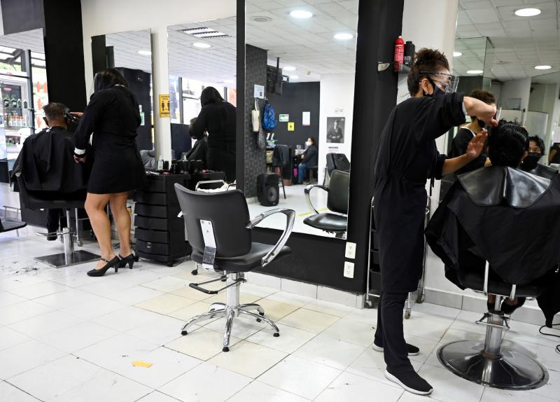 Employees at a beauty salon wear protetive gear while doin haircuts, during the COVID-19 pandemic, in Mexico City on June 29, 2020. - Starting this week Mexico City is allowing the reopening of shops, street markets and athletic complexes but with limited capacity and hours. Hotels and restaurants in the capital will reopen at about 30% seating capacity. (Photo by ALFREDO ESTRELLA / AFP) (Photo by ALFREDO ESTRELLA/AFP via Getty Images)