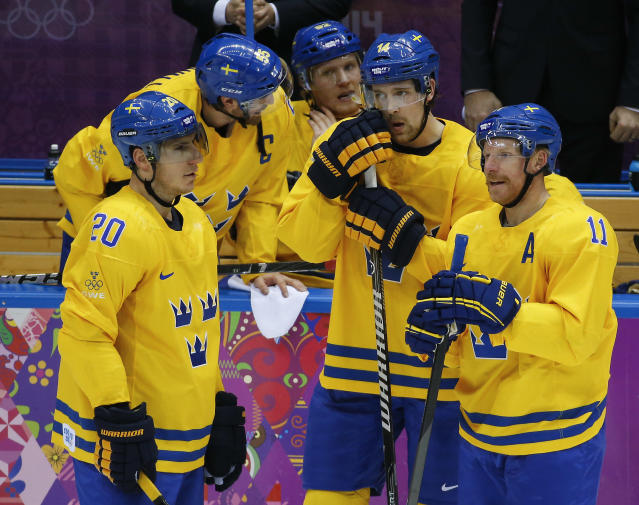 Sweden players talk during a break in the first period of a men's quarterfinal ice hockey game against Slovenia at the 2014 Winter Olympics, Wednesday, Feb. 19, 2014, in Sochi, Russia. (AP Photo/Mark Humphrey)