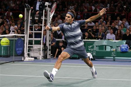 Roger Federer of Switzerland hits a return to Novak Djokovic of Serbia in their semi-final match of the Paris Masters men's singles tennis tournament at the Palais Omnisports of Bercy in Paris, November 2, 2013. REUTERS/Gonzalo Fuentes