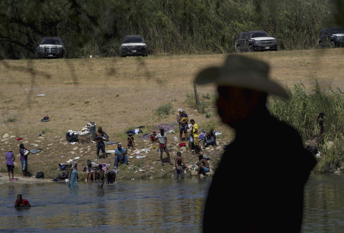 FILE - In this Sept. 22, 2021, file photo migrants, many from Haiti, wade across the Rio Grande from Del Rio, Texas, to return to Ciudad Acuna, some to avoid possible deportation from the U.S. and others to get supplies. In the past week, the push to change the nation's immigration laws and create a path to citizenship for young immigrants brought illegally to the country as children faced a serious setback on Capitol Hill. Bipartisan negotiations to overhaul policing collapsed and searing images of Haitian refugees being mistreated at the U.S.-Mexico border undermined President Joe Biden's pledge of humane treatment for those seeking to enter the United States. (AP Photo/Fernando Llano, File)