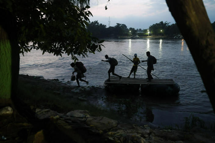 Migrants on rafts reach the Mexico shore after crossing the Suchiate River from Guatemala, near Ciudad Hidalgo, Mexico, Wednesday, June 5, 2019. Hundreds more Central American migrants have crossed into Mexico from Guatemala, and a group of about 1,000 have started walking en mass to the north. (AP Photo/Marco Ugarte)