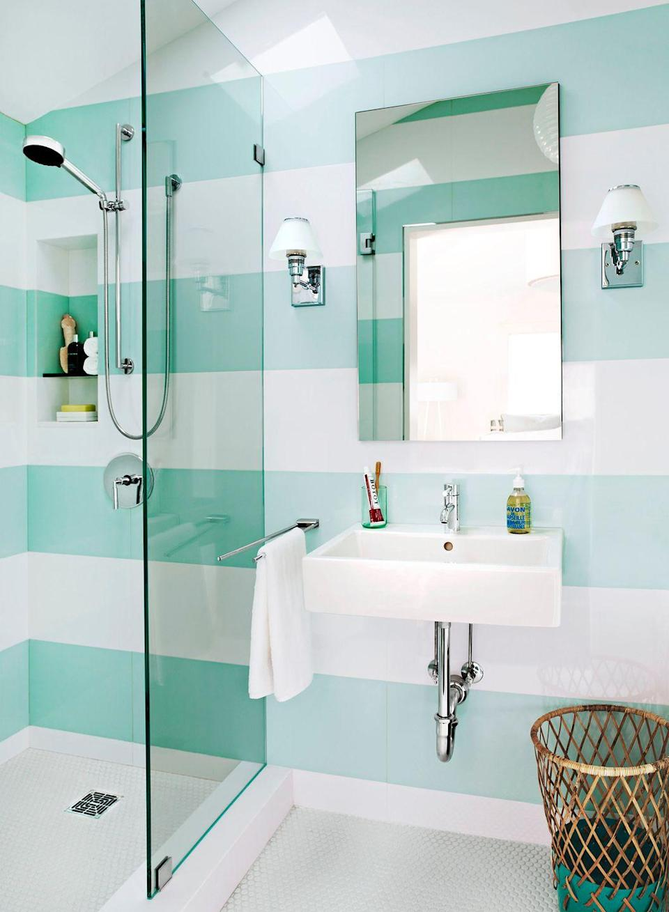 <p>Neutral floor tiles serve as the perfect counterpoint to this bathroom's bold striped walls. </p>