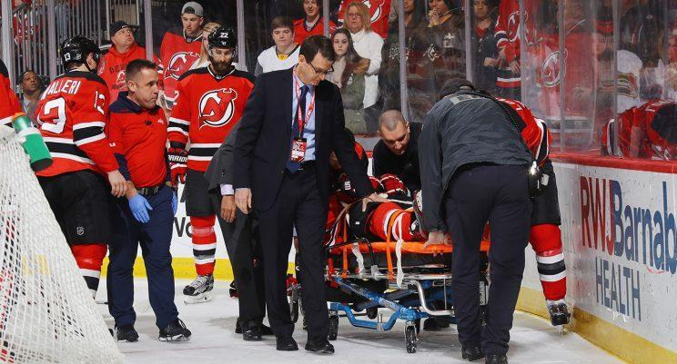 John Moore is stretchered off the ice following a hit from Tom Wilson. (Bruce Bennett/Getty Images)