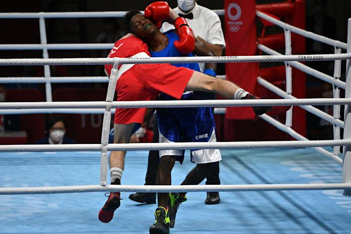 <p>Ireland's Aidan Walsh (red) and Cameroon's Albert Mengue Ayissi fight during their men's welter (63-69kg) preliminaries round of 16 boxing match during the Tokyo 2020 Olympic Games at the Kokugikan Arena in Tokyo on July 27, 2021. (Photo by Luis ROBAYO / AFP)</p>