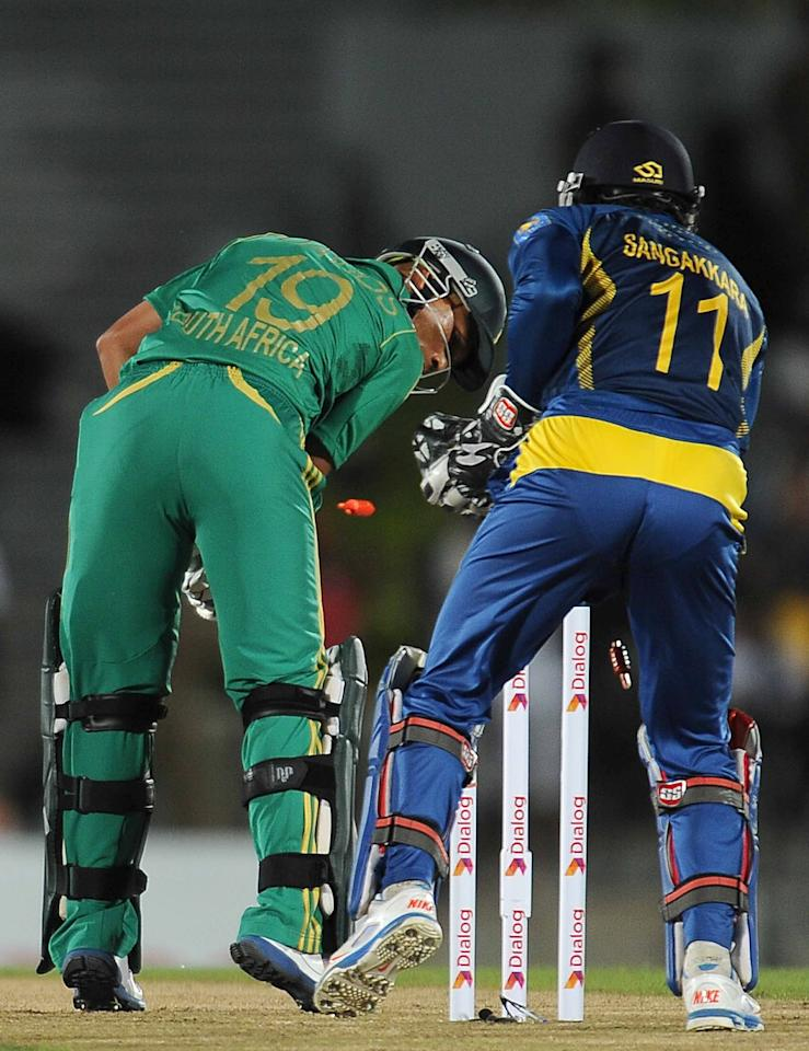 South African batsman Henry Davids (L) is dismissed by Sri Lankan cricketer Nuan Kulasekara as wicketkeeper Kumar Sangakkara (R) looks on during the second Twenty20 cricket match between Sri Lanka and South Africa at the Suriyawewa Mahinda Rajapakse International Cricket Stadium in the southern district of Hambantota on August 4, 2013.  AFP PHOTO / LAKRUWAN WANNIARACHCHI