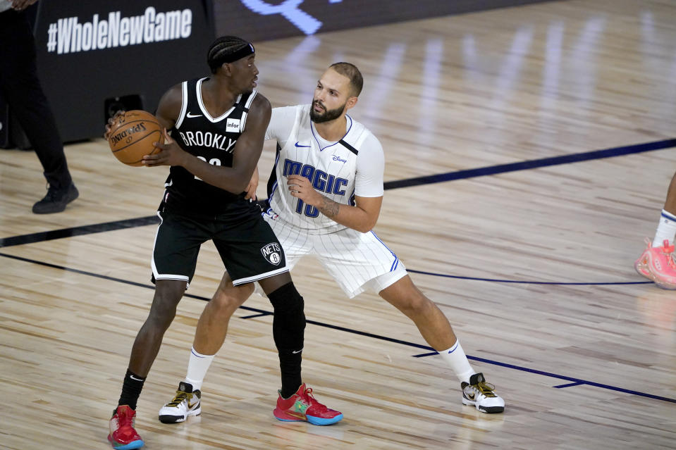 Brooklyn Nets' Caris LeVert, left, looks to pass as Orlando Magic's Evan Fournier defends during the second half of an NBA basketball game Friday, July 31, 2020, in Lake Buena Vista, Fla. (AP Photo/Ashley Landis, Pool)