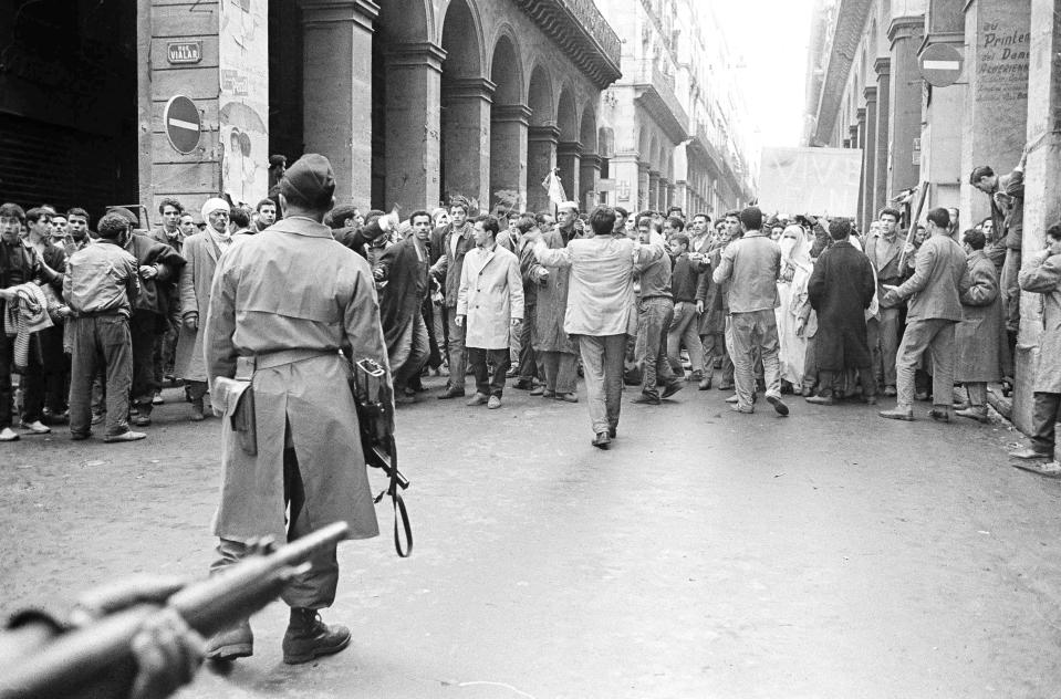 FILE - In this Dec.14, 1960 file photo, armed French soldiers, foreground, face a shouting mob of Algerians at an entrance to the Casbah native quarter in Algiers. French President Emmanuel Macron announced a decision to speed up the declassification of secret documents related to Algeria's seven-year war of independence from 1954 to 1962. (AP Photo, File)