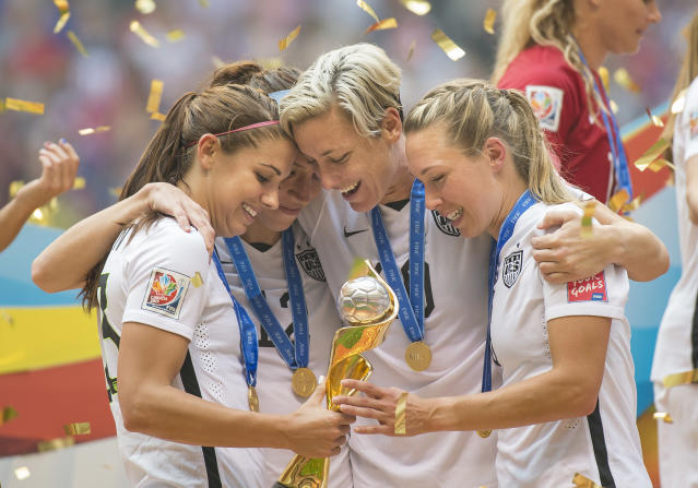 Alex Morgan (left), Lauren Holiday, Abby Wambach, and Whitney Engen celebrate with the World Cup trophy in 2015. (Photo by Christopher Morris/Corbis via Getty Images)