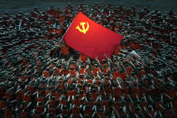 Performers dressed as rescue workers gather around the Communist Party flag during a gala show ahead of the 100th anniversary of the founding of the Chinese Communist Party in Beijing on Monday, June 28, 2021. China is marking the centenary of its ruling Communist Party this week by heralding what it says is its growing influence abroad, along with success in battling corruption at home. (AP Photo/Ng Han Guan)