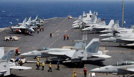 FILE PHOTO - U.S. Navy personnel prepare to launch an F18 fighter jet on the deck of USS Carl Vinson during a routine exercise in South China Sea, March 3, 2017. REUTERS/Erik De Castro/File Photo