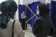 Chechen women wait to fill their ballots in a voting booth at a polling station during the Parliamentary elections in Grozny, Russia, Friday, Sept. 17, 2021. Russia has begun three days of voting for a new parliament that is unlikely to change the country's political complexion. There's no expectation that United Russia, the party devoted to President Vladimir Putin, will lose its dominance in the State Duma. (AP Photo/Musa Sadulayev)