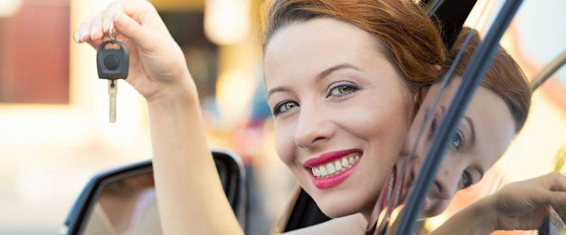 Closeup portrait happy, smiling, young attractive woman, buyer sitting in her new blue car showing keys isolated outside dealer