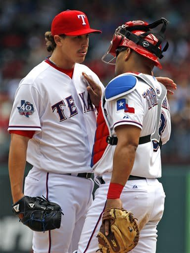 Texas Rangers starting pitcher Derek Holland, left, talks to catcher Yorvit Torrealba, right, just before being pulled in the eighth inning of a baseball game against the Seattle Mariners, Thursday, April 12, 2012, in Arlington, Texas. The Rangers won 5-3. (AP Photo/Tony Gutierrez)