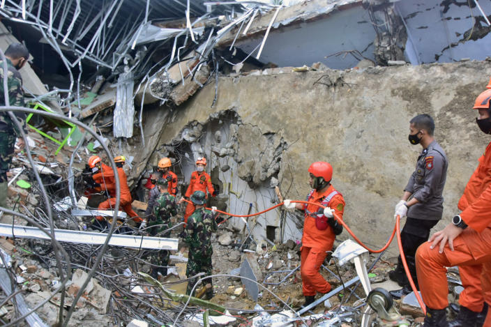 Rescuers search for survivors at the ruin of a government building collapsed during an earthquake in Mamuju, West Sulawesi, Indonesia, Friday, Jan. 15, 2021. A strong, shallow earthquake shook Indonesia's Sulawesi island just after midnight Friday, toppling homes and buildings, triggering landslides and killing a number of people. (AP Photo/Daus Thobelulu)