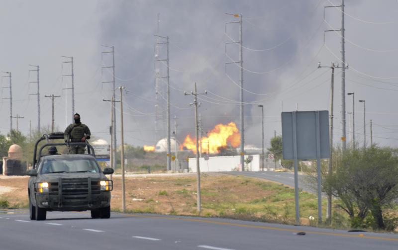 A Mexican army vehicle patrols on a road as fire and smoke rise from a gas pipeline distribution center in Reynosa, Mexico near Mexico's border with the United States, Tuesday Sept. 18, 2012. Mexico's state-owned oil company, Petroleos Mexicanos, also known as Pemex said the fire had been extinguished and the pipeline had been shut off but ten people were killed during the incident. (AP Photo/El Manana de Reynosa)