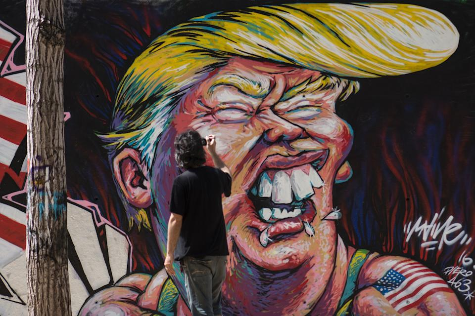 A man takes pictures of a graffiti of Republican presidential candidate Donald Trump in Barcelona on June 7, 2016.