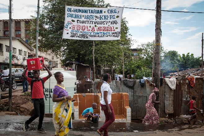 People walk in front of a banner warning against the deadly Ebola virus on October 4, 2014 in a street of Freetown (AFP Photo/Florian Plaucheur)
