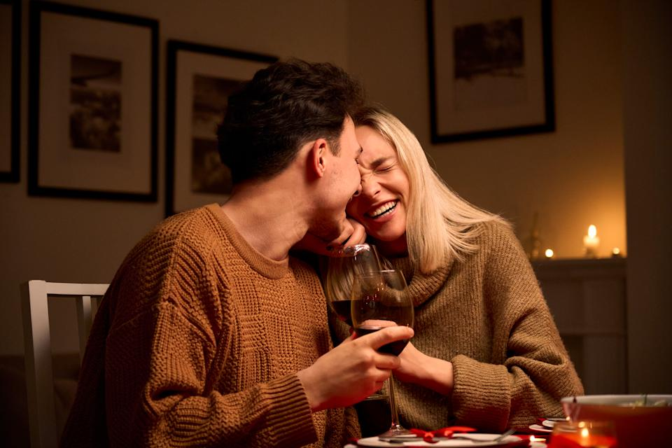 Happy young couple in love hugging, laughing, drinking wine, enjoying talking, having fun together celebrating Valentines day dining at home, having romantic dinner date with candles sitting at table.