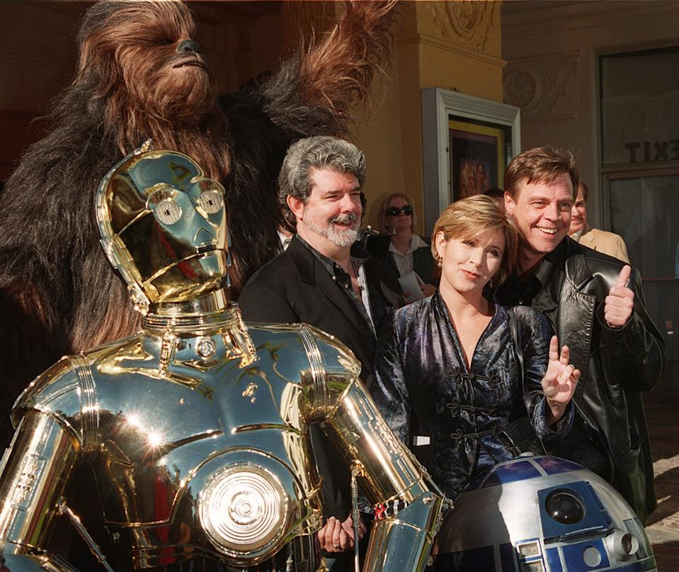 "Characters from the film ""Star Wars"" join writer and director George Lucas, left, Carrie Fisher, center, and Mark Hamill at the world premiere of ""Star Wars Special Edition"" Saturday, Jan. 18, 1997, in the Westwood section of Los Angeles.  The movie  was first released 20 years ago. (AP Photo/Rene Macura)"
