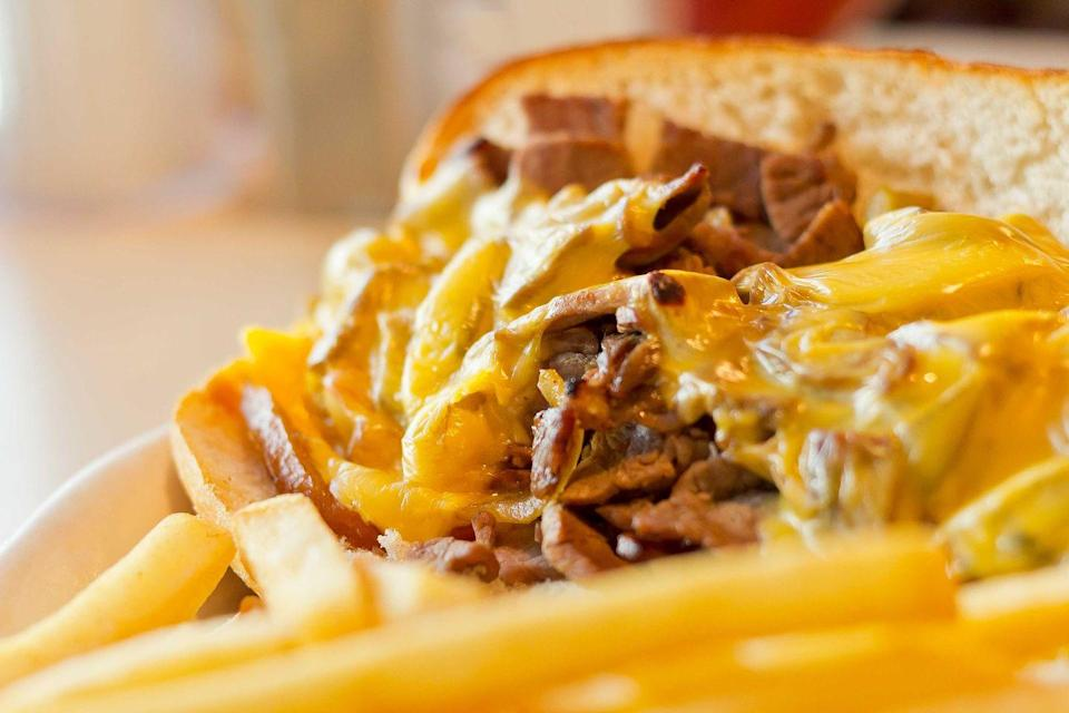 """<p><strong>Philly Cheesesteak</strong></p><p>This one is a no-brainer. A visit to Philly isn't a proper one without trying a proper Philly Cheesesteak. We know, we know, <a href=""""https://www.genosteaks.com/"""" rel=""""nofollow noopener"""" target=""""_blank"""" data-ylk=""""slk:Geno's"""" class=""""link rapid-noclick-resp"""">Geno's</a> or <a href=""""https://www.patskingofsteaks.com/"""" rel=""""nofollow noopener"""" target=""""_blank"""" data-ylk=""""slk:Pat's"""" class=""""link rapid-noclick-resp"""">Pat's</a>? Here's a secret -- both iconic restaurants are amazing, but this friendly camaraderie probably boosts sales for both. </p>"""