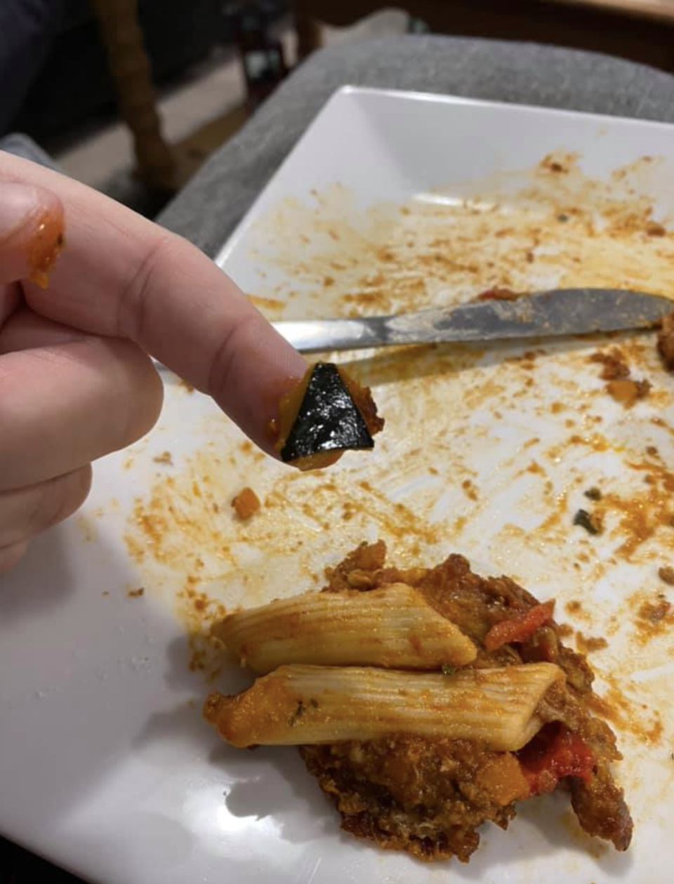 A black object is displayed on a person's finger above a plate with pasta on it.