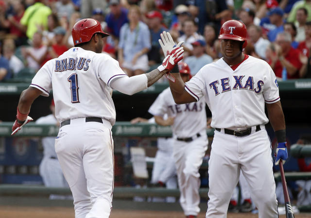 Texas Rangers' Elvis Andrus (1) is congratulated by Adrian Beltre, left, after scoring a run against the Los Angeles Angels during the first inning of a baseball game, Tuesday, July 30, 2013, in Arlington, Texas. (AP Photo/Jim Cowsert)