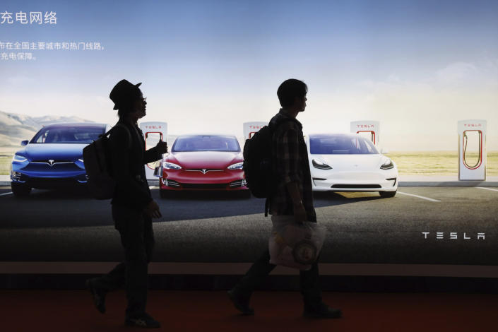In this April 17, 2019, photo, attendees walks past advertisement for electric cars from Tesla at the Auto Shanghai 2019 show in Shanghai. China's electric car sales are stalling following the end of multibillion-dollar subsidies that made it the biggest market for the technology. Communist leaders want to make China a leader in electric cars but are shifting the burden to the industry by imposing mandatory sales quotas. (AP Photo/Ng Han Guan)