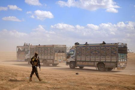 FILE PHOTO: A fighter from the Syrian Democratic Forces (SDF) walks in front of two trucks, near the village of Baghouz, Deir Al Zor province, in Syria March 7, 2019.  REUTERS/Rodi Said