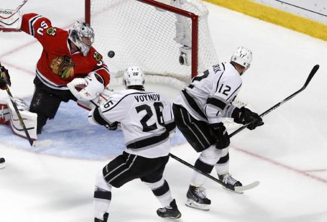 Los Angeles Kings right wing Marian Gaborik (12) scores a goal against Chicago Blackhawks goalie Corey Crawford (50) as the Kings defenseman Slava Voynov (26) watches during the third period in Game 7 of the Western Conference finals in the NHL hockey Stanley Cup playoffs Sunday, June 1, 2014, in Chicago. (AP Photo/Charles Rex Arbogast)