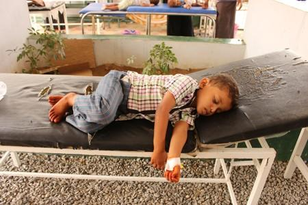 A boy, cholera patient, lies on a bed as he receives medical care at a health center in the village of Islim, in the northwestern province of Hajjah