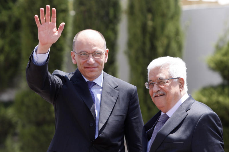 Italian Prime Minister Enrico Letta, left, waves as he walks with Palestinian President Mahmoud Abbas during a welcome ceremony in the West Bank city of Ramallah Tuesday, July 2, 2013. (AP Photo/Majdi Mohammed)