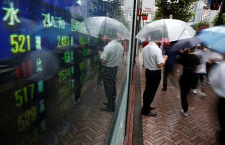 File Photo - A man stands next to an electronic board showing stock prices in Tokyo, Japan, August 18, 2016. REUTERS/Kim Kyung-Hoon