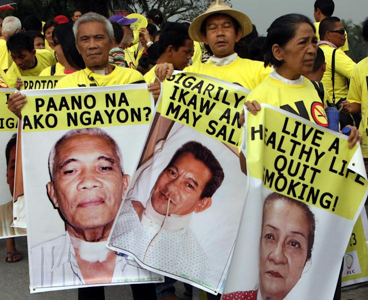 """Victims of tobacco-related diseases holding their pictures, march towards the Philippine International Convention Center where ProTobEx, a large international tobacco fair is held, in suburban Pasay city, south of Manila Thursday, March 15, 2012. Anti-smoking advocates have picketed the tobacco fair in the Philippines that has emerged as a battleground for the industry. Words on a banner, left, reads """"What happens to me now?"""" and """"Cigarettes you are the culprit"""". (AP Photo/Pat Roque)"""