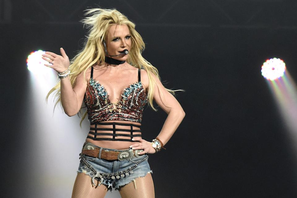 Britney performing on stage in denim shorts and a bra top