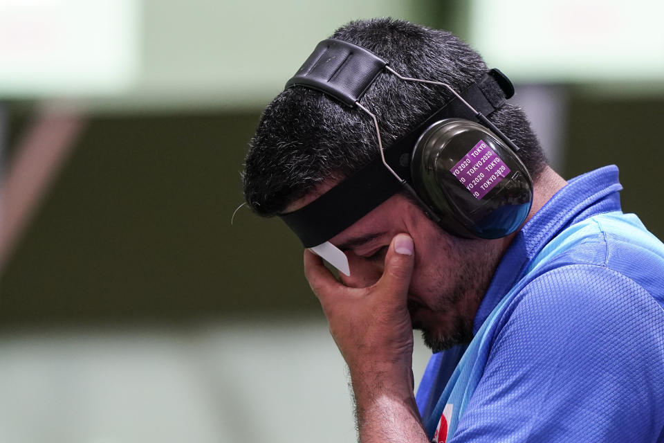 Javad Foroughi, of Iran, pauses as he competes in the men's 10-meter air pistol at the Asaka Shooting Range in the 2020 Summer Olympics, Saturday, July 24, 2021, in Tokyo, Japan. (AP Photo/Alex Brandon)